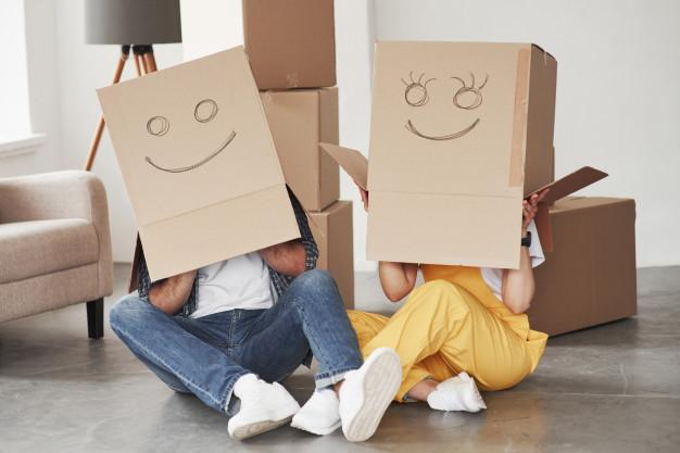 Cute smiles on boxes that is on the heads. happy couple together in their new house. conception of moving Free Photo